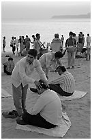 Head rub given by malish-wallah, Chowpatty Beach. Mumbai, Maharashtra, India ( black and white)