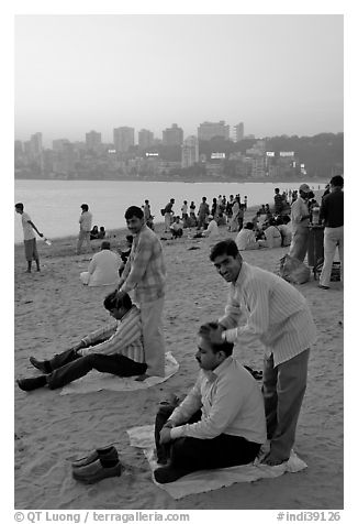 Head masseurs and Mumbai skyline at sunset,  Chowpatty Beach. Mumbai, Maharashtra, India (black and white)