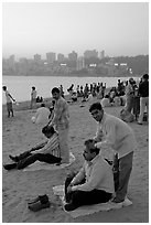 Head masseurs and Mumbai skyline at sunset,  Chowpatty Beach. Mumbai, Maharashtra, India ( black and white)