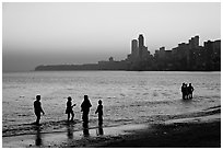 People standing in water at sunset with skyline behind, Chowpatty Beach. Mumbai, Maharashtra, India ( black and white)