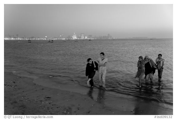 Women walking in water by night, Chowpatty Beach. Mumbai, Maharashtra, India (black and white)