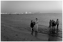 Women walking in water by night, Chowpatty Beach. Mumbai, Maharashtra, India ( black and white)