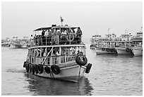 Tour boat loaded with passengers. Mumbai, Maharashtra, India ( black and white)