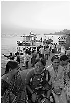 Women sitting on waterfront with boats behind at twilight. Mumbai, Maharashtra, India ( black and white)