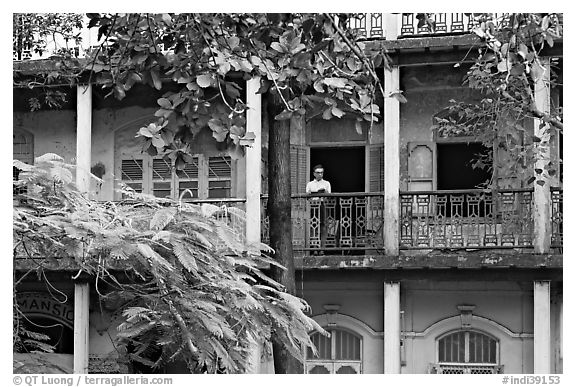 Facade with balconies and man reading. Mumbai, Maharashtra, India (black and white)