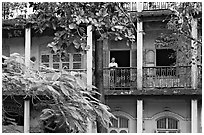Facade with balconies and man reading. Mumbai, Maharashtra, India ( black and white)