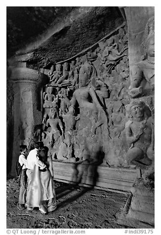 Family looking at Ardhanarishwar Siva sculpture, main Elephanta cave. Mumbai, Maharashtra, India (black and white)