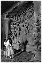 Family looking at Ardhanarishwar Siva sculpture, main Elephanta cave. Mumbai, Maharashtra, India ( black and white)