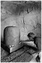Man venerating a Linga in Shiva shrine, Elephanta Island. Mumbai, Maharashtra, India ( black and white)