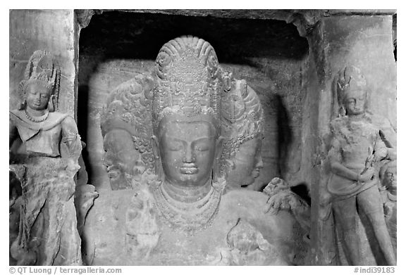 Trimurti flanked by pilasters with figures of dwarplalas, Elephanta caves. Mumbai, Maharashtra, India (black and white)