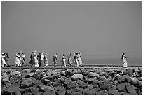 Women walking on  jetty in the distance, Elephanta Island. Mumbai, Maharashtra, India (black and white)