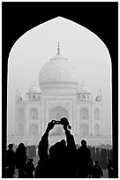 Visitor pointing  digital camera to Maj Mahal, framed by arch of gateway. Agra, Uttar Pradesh, India (black and white)