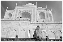 Woman sitting at the base of Taj Mahal looking up. Agra, Uttar Pradesh, India (black and white)