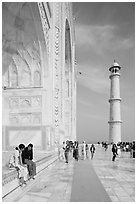Couple sitting on side pishtaq and visitors strolling on platform, Taj Mahal. Agra, Uttar Pradesh, India (black and white)