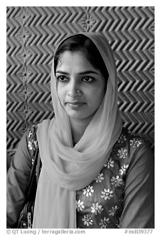 Young woman with bright scarf, in front of Rumi Sultana motifs. Fatehpur Sikri, Uttar Pradesh, India (black and white)