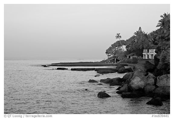 Boulders, beachfront house, and palm trees at sunrise. Goa, India (black and white)
