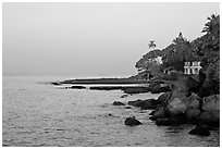 Boulders, beachfront house, and palm trees at sunrise. Goa, India ( black and white)