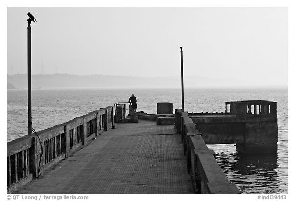 Pier with man fishing, early morning, Dona Paula. Goa, India (black and white)