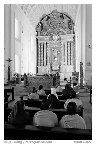 Indian women sitting in front of the altar, Basilica of Bom Jesus, Old Goa. Goa, India (black and white)