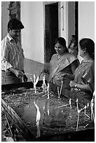 Man and two women burning candles, Basilica of Bom Jesus, Old Goa. Goa, India (black and white)