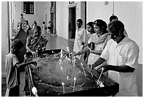 Indian people burning candles, Basilica of Bom Jesus, Old Goa. Goa, India ( black and white)