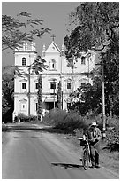 Man walking a bicycle in front of church of St John, Old Goa. Goa, India ( black and white)