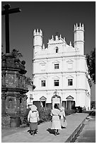 Women walking towards Church of St Francis of Assisi, afternoon, Old Goa. Goa, India (black and white)