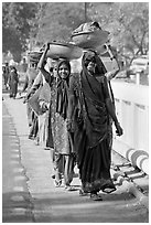 Women walking in line carrying baskets on heads. Khajuraho, Madhya Pradesh, India (black and white)