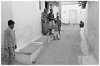 Family in village alley. Khajuraho, Madhya Pradesh, India ( black and white)
