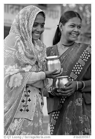 Women with pots used for religious offerings. Khajuraho, Madhya Pradesh, India (black and white)