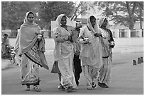 Hindu women walking in street with pots. Khajuraho, Madhya Pradesh, India (black and white)