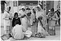 Hindu women purchasing offerings before going to temple. Khajuraho, Madhya Pradesh, India ( black and white)