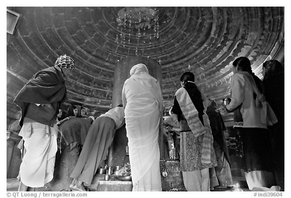 Worshipers and polished lingam inside Matangesvara temple. Khajuraho, Madhya Pradesh, India (black and white)