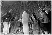 Worshipers and polished lingam inside Matangesvara temple. Khajuraho, Madhya Pradesh, India ( black and white)