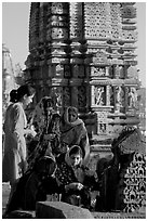 Women offering morning puja  in front temple spire. Khajuraho, Madhya Pradesh, India ( black and white)
