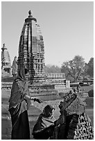 Women worshipping image with temple spire behind. Khajuraho, Madhya Pradesh, India ( black and white)