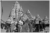 Worshippers making offering with Lakshmana temple behind. Khajuraho, Madhya Pradesh, India (black and white)