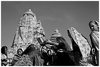 Hindu women making offerings to image with Lakshmana temple behind. Khajuraho, Madhya Pradesh, India ( black and white)