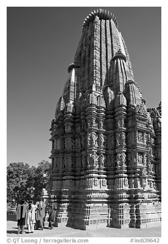 Women walking at the base of the sikhara of Devi Jagadamba temple. Khajuraho, Madhya Pradesh, India (black and white)