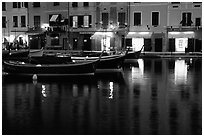 Light of shops reflected in harbor at dusk, Portofino. Liguria, Italy ( black and white)