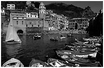 Colorful fishing boats in the harbor and Piazza Guglielmo Marconi, Vernazza. Cinque Terre, Liguria, Italy (black and white)