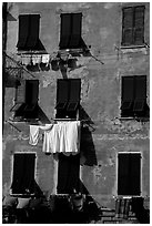 Typical terra cotta facade with hanging laundry and green shutters, Vernazza. Cinque Terre, Liguria, Italy ( black and white)