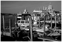 Water taxi driver cleaning out his boat in the morning, Santa Maria della Salute in the background. Venice, Veneto, Italy (black and white)