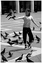 Girl playing with the pigeons, Piazzetta San Marco (Square Saint Mark), mid-day. Venice, Veneto, Italy (black and white)
