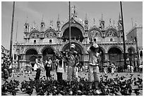 Children feeding flock of pigeon, in front of the Basilica San Marco, mid-day. Venice, Veneto, Italy (black and white)