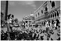 Visitors feeding  pigeons, Piazzetta San Marco (Square Saint Mark), mid-day. Venice, Veneto, Italy (black and white)