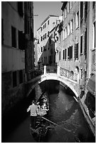 Gondola tour in a picturesque canal with bridge. Venice, Veneto, Italy ( black and white)