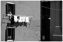 Woman hangs laundry to dry, Burano. Venice, Veneto, Italy (black and white)