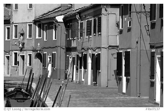 Sidewalk and row of brightly painted houses, Burano. Venice, Veneto, Italy (black and white)