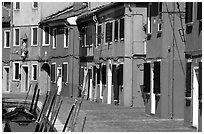 Sidewalk and row of brightly painted houses, Burano. Venice, Veneto, Italy ( black and white)